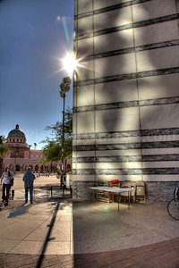 The sun captured peaking around Tucson's DT library.