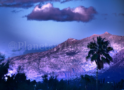 A mystical cloud hovers over a purple and lavender mountain in Tucson.