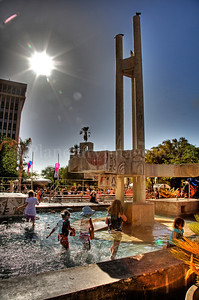 The hot late-day sun shines over a fountain where children play at the Tucson Folk Festival