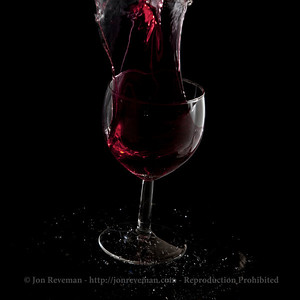 Wine glass bouncing of a dark, wet, surface.