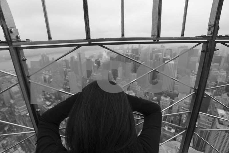 A woman holds her hands to shield eyes at the Empire State Building as she gazes over New York City.