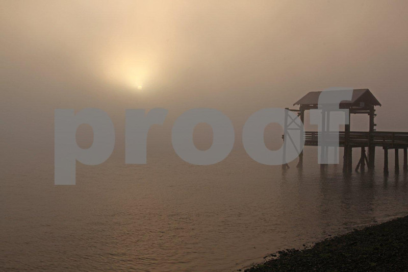 The sun peeks through the morning fog at dock side.