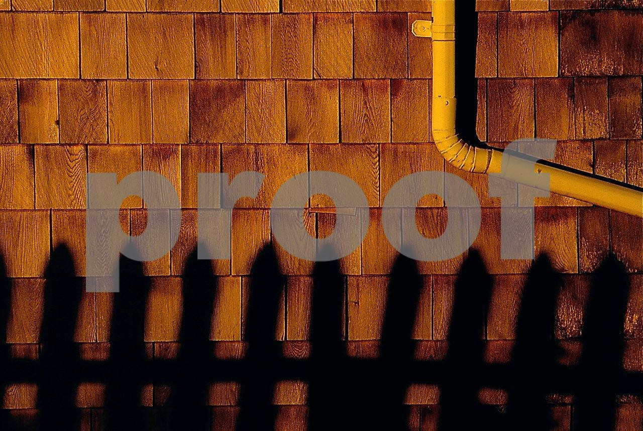 The shadow from a fence projected on a building with wood shake siding.