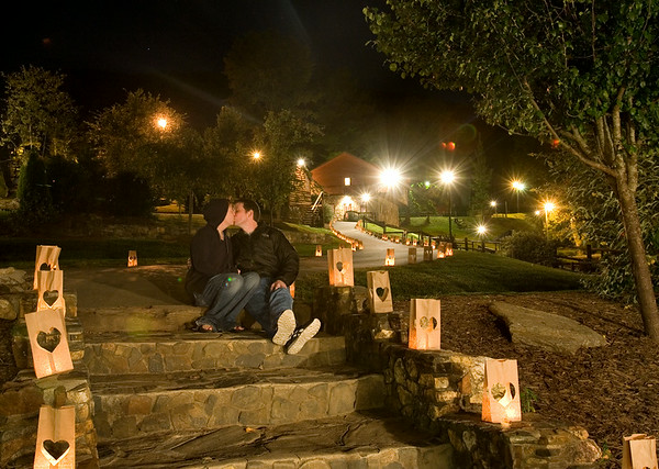 A young couple smooches on stone steps at a couple's retreat in the mountains surrounded by heart shapped luminaries.  (Jenni Farrow)