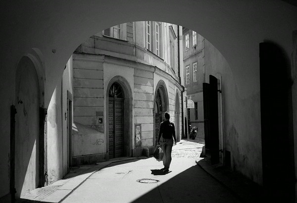 A woman walks down a street in Prague, Czech Republic.  A scanned negative.  Sam Abell called this a successful image.