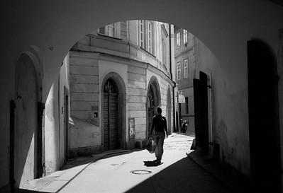 A woman walks down a street in Prague, Czech Republic.
