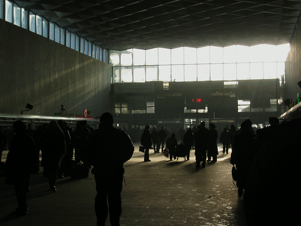Travelers walk in the dark train station in St. Petersburg, Russia with the sun pouring in frosted windows from the extreem cold.  (Jenni Farrow)