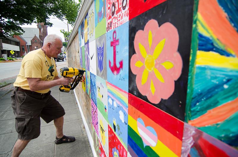 City Councilor Joel Kaddy installs the new Building Blocks tiles on Main Street on Friday afternoon. SENTINEL & ENTERPRISE / Ashley Green