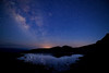 A high lake in the Maroon Bell Wilderness reflects the night sky.