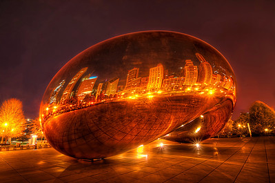 "Cloud Gate, a public sculpture by Indian-born British artist Anish Kapoor, is the centerpiece of the AT&T Plaza in Millennium Park within the Loop community area of Chicago, Illinois, United States. The sculpture and AT&T Plaza are located on top of Park Grill, between the Chase Promenade and McCormick Tribune Plaza & Ice Rink. Constructed between 2004 and 2006, the sculpture is nicknamed ""The Bean"" because of its bean-like shape. Made up of 168 stainless steel plates welded together, its highly polished exterior has no visible seams. It is 33 by 66 by 42 feet (10 by 20 by 13 m), and weighs 110 short tons (100 t; 98 long tons).  Said to have been inspired by liquid mercury,[1] the sculpture's surface reflects and distorts the city's skyline. Visitors are able to walk around and under Cloud Gate's 12-foot (3.7 m) high arch. On the underside is the ""omphalos"" (Greek for ""navel""), a concave chamber that warps and multiplies reflections. The sculpture builds upon many of Kapoor's artistic themes, and is popular with tourists as a photo-taking opportunity for its unique reflective properties.  The sculpture was selected during a design competition. After Kapoor's design was chosen, numerous technological concerns regarding the design's construction and assembly arose, in addition to concerns regarding the sculpture's upkeep and maintenance. Various experts were consulted, some of whom believed the design could not be implemented. Eventually, a feasible method was found, but the sculpture's construction fell behind schedule. It was unveiled in an incomplete form during the Millennium Park grand opening celebration in 2004, before being concealed again while it was completed. Cloud Gate was formally dedicated on May 15, 2006, and has since gained considerable popularity, both domestically and internationally.  Equipment=Nikon D7000 Lens Used=Tamron SP AF 10-24mm F/3.5-4.5 Lens Exposures=7 Location=Chicago,Illinois  Workflow= PhotoMatix 4.2 Adobe PhotoShop Cs6 Adobe Light room 4.1 Software, Nik Color Efex=Glamor Glow, and Tonal Contrast Topaz Adjust= Mild Details and Photo Pop"