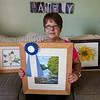 Leominster Art Association member Cindi Peterson shows off her artwork in her Lunenburg home on Tuesday afternoon. SENTINEL & ENTERPRISE / Ashley Green