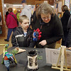 Kaleb Elliott, 6, and his grandmother Colleen Stone look at some of the at work at the second annual art show for city students from elementary through high school at Leominster City Hall Tata Auditorium on Wednesday night. SENTINEL & ENTERPRISE/JOHN LOVE