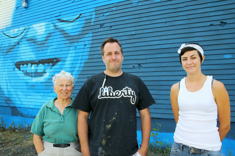 Marion Stoddard, an environmentalist who was instrumental in cleaning up the Nashua River, visited the Fitchburg mural honoring her on Tuesday to see it for the first time. She posed with artists Jon Allen, 38, and Sophy Tuttle, 27, with her face half painted behind her. SENTINEL & ENTERPRISE/JOHN LOVE