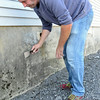Local artist Jon Allen talks scrapes mold off the foundation of the old Gamche's Cyclery building in preparation for upcoming mural honoring Marion Stoddart, an environmentalist who was instrumental in cleaning up the Nashua River. SENTINEL & ENTERPRISE / Ashley Green