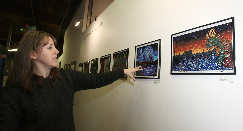 ". Artist Tracy Levesque with her series of limited edition prints of monsters attacking Lowell landmarks, including ""Yeti Eats Downtown Lowell\"" and \""IT Came from the Merrimack.\"" (SUN/Julia Malakie)"