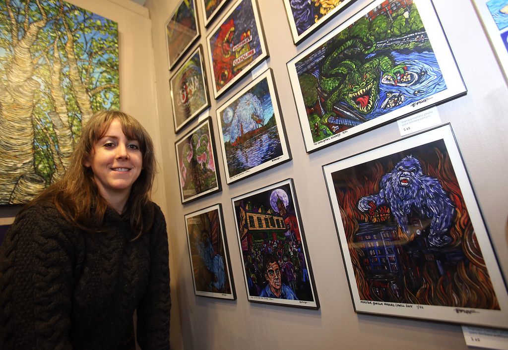 ". Artist Tracy Levesque with her series of limited edition prints of monsters attacking Lowell landmarks, including ""Monster Gorilla Attacks Lowell Sun.\"" (SUN/Julia Malakie)"