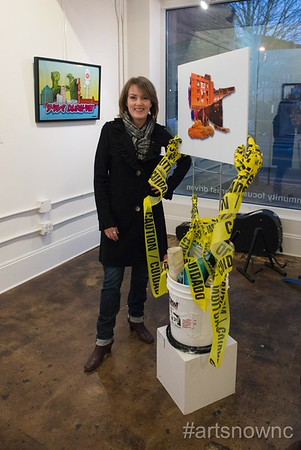 "Artist Carin Walsh stands with her piece ""COMMUNITY FAIL"" at the ""Durham Under Development"" exhibition at Pleiades Gallery."