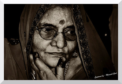 Rajasthani woman (in all her finery) caught in a pensive mood!