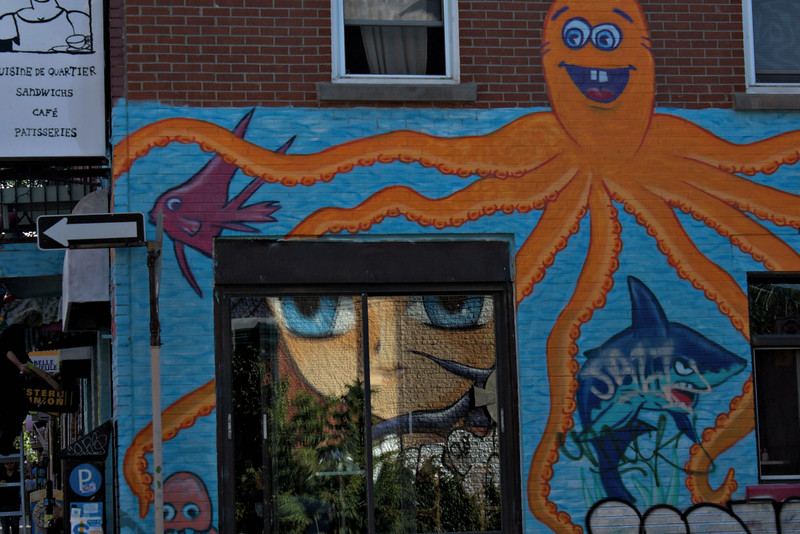 Graffiti art reflected in window of mural-decorated restaurant in Montreal.