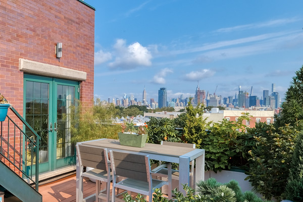 A green roof deck perfect for enjoying an NYC cityscape over a galss of wine and some small bites.