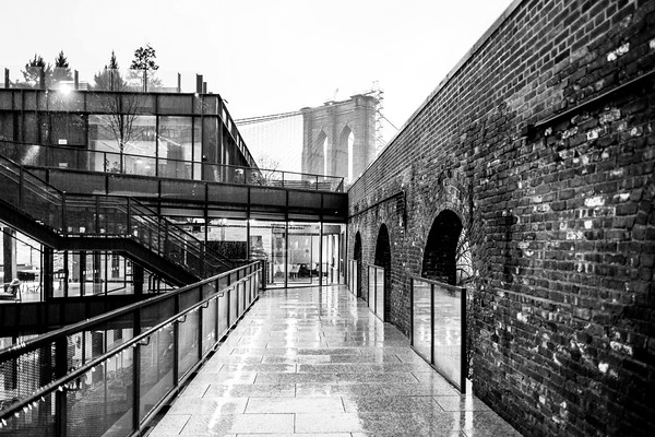 An open air architetural view of an exposed brick warehouse in DUMBO with the Brooklyn Bridge overlooking the scene.