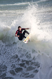 Surfer shredding a wave off of the Huntington Beach Pier.