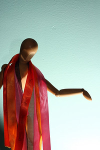 A drawing model, draped in ribbons.