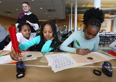 Tsongas Industrial History Center hosts Old Tyme Art, for kids to learn how to write with quill pens, and get their silhouettes drawn, as part of Kids Week during school vacation week. From left, Talia Njui, 10, her sister Imani Njui, 9,  and their cousin Mikayla Mwangi, 13, all of Lowell. (SUN/Julia Malakie)