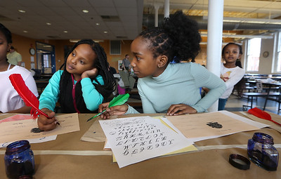 Tsongas Industrial History Center hosts Old Tyme Art, for kids to learn how to write with quill pens, and get their silhouettes drawn, as part of Kids Week during school vacation week. From left, Imani Njui, 9, her cousin Mikayla Mwangi, 13, and sister Bella Njui, 6, rear, all of Lowell. (SUN/Julia Malakie)