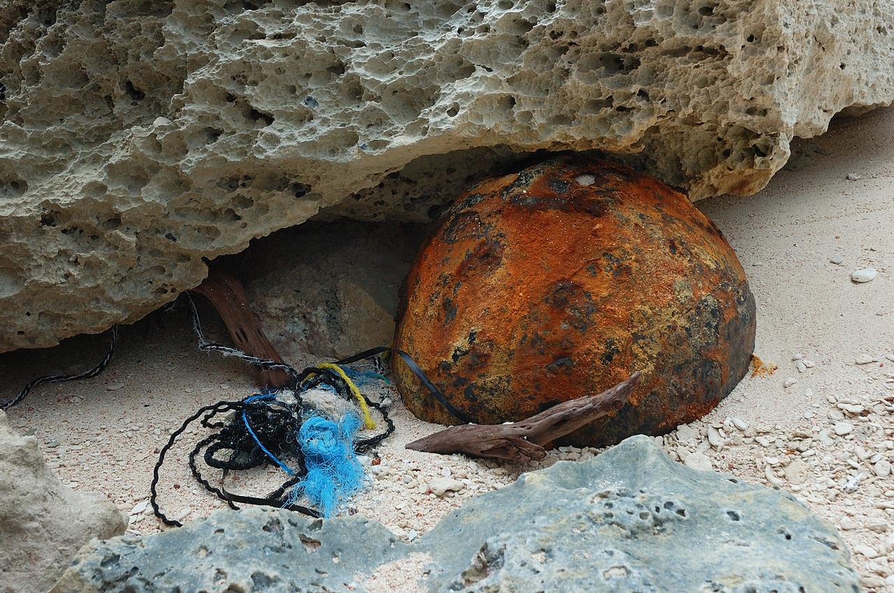 """Bermuda, Astwood Cove: cordages, une pièce de platique foncée, une vieille branche et une sphère de métal rouillée ( 18"""" diam.environ ) sous un rocher sur la plage, la couleur bleu du rocher en premier plan est celle que j'ai observé au moment de la photo / 3 ropes, a dark piece of plactic, an old piece of a tree and a rust metal sphere ( 18"""" diam. app. ) under a rock on the beach, the blue color of the roch in foreground is his true color."""