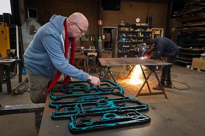 © Wim van Vossen Fotografie - DIRKSLAND - Jaap Reedijk is de koffers aan het uittekenen op staalplaat die op het perron moeten komen te staan aan het Havenhoofd in Middelharnis. Een van de Gebroeders de Roon is het ontwerp aan het snijden met een snijbrander.