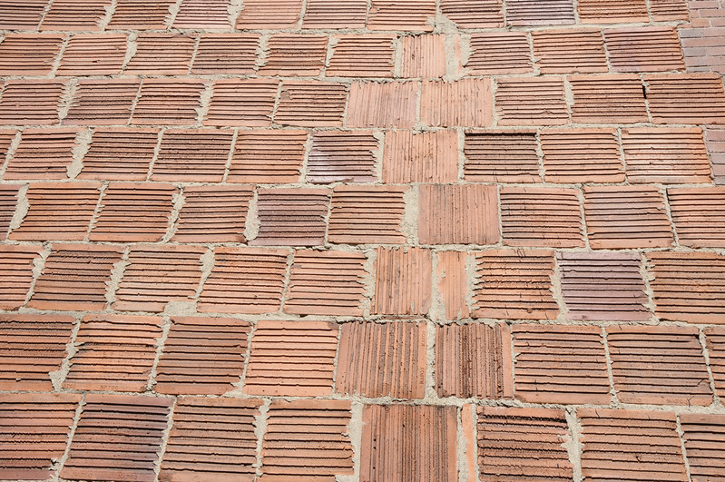 Wall made from red bricks with interesting pattern on exposed brick face