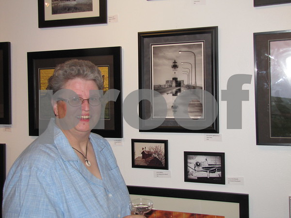 Tedra Towne, local photographer, stands near her photos of lighthouses at Permanent Collection Gallery Art.