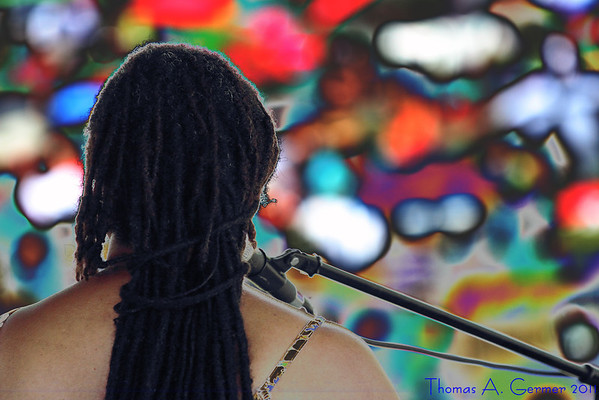 """7/18/2011: Taken at the Linganore Winery Reggae Festival (Mt. Airy, MD).  The singer/keyboardist and her microphone were seriously underexposed and was just a silhouette against the sea of out-of-focus people. Thanks to taking the data RAW, her braids were still there. Accidentally made the histogram adjustment non-monotonic (mathematical-speak for not just going up or not just going down, in this case, an S curve) and got this effect.    See the rest of the gallery at <a href=""""http://www.tagermer.com/Friends/Linganore-July-2011/18085875_G9ggZq"""">Linganore July 2011</a>."""