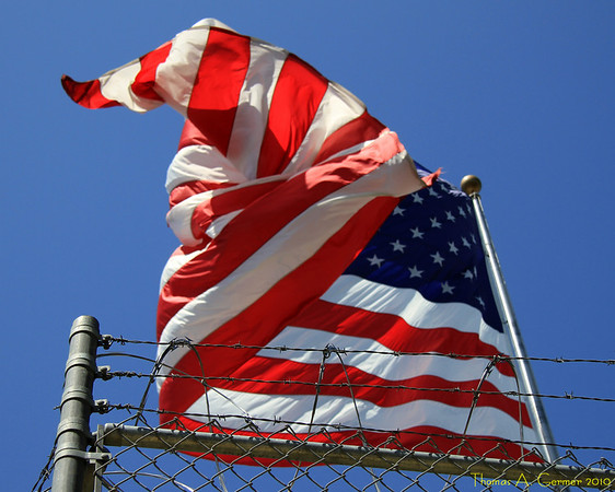 Flag with barbed wire.<br /> <br /> I shot this in Campbell, CA.  I like the image of freedom combined with restriction.