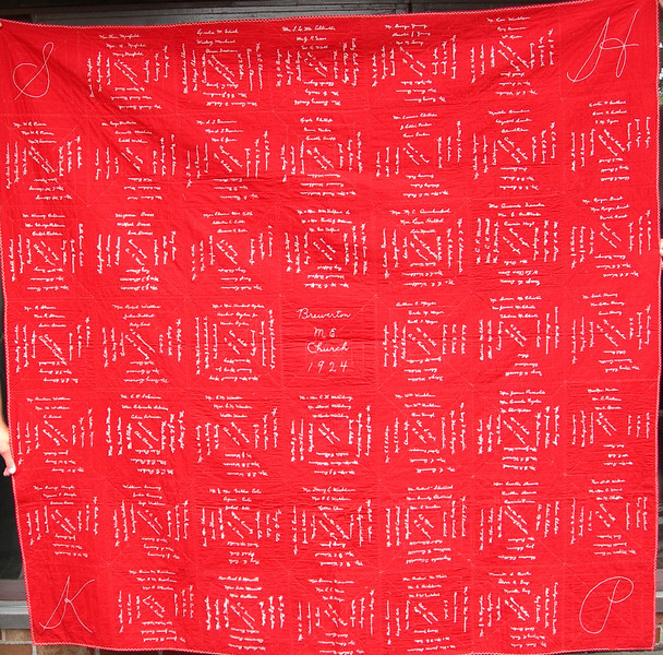 """A so-called """"Tithing Quilt"""", this one made in Brewerton, New York in 1924 by the ladies whose initials appear in the corners.  These were used to raise money for churches, in this case the Methodist Episcopal Church of Brewerton.  Each person who wanted to contribute would pay a set amount of money (often sums like 5, 10 or 25 cents) and expert sewers would embroider their name on the quilt.  The next picture is a close-up of the center dedication."""