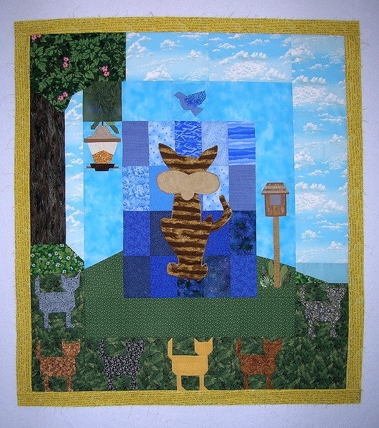 "I hit a creativity brick wall with this one. I felt the story told by DD, Ann and Joan's work could stand alone, and I wanted to ""stop the action"". I simply added a three inch border of yellow fabric that's imprinted with ""cat-speak"" words."