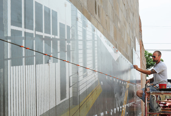 Globe/T. Rob Brown<br /> Branden Yost of Joplin, an RC Tile & Hardwoods installer, adds another tile to a Route 66 mural in downtown Galena, Kan., Tuesday afternoon, June 26, 2013. The mural, designed by art director Chris Auckerman and graphic designer Jon White, both with Images in Tile owned by Paul Whitehill, is located at the intersection of 7th and Main streets in Galena. The portion on the left features the haunted bordello.