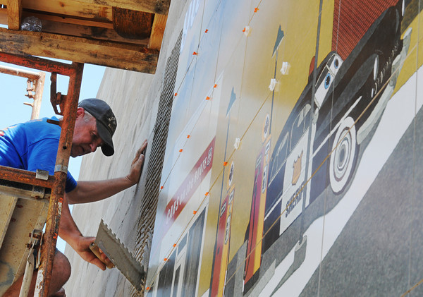 Globe/T. Rob Brown<br /> Randy Wagner, owner of RC Tile & Hardwoods, adds cement to a wall before adding more tiles to a Route 66 mural in downtown Galena, Kan., Wednesday afternoon, June 27, 2013. The mural, designed by art director Chris Auckerman and graphic designer Jon White, both with Images in Tile owned by Paul Whitehill, is located at the intersection of 7th and Main streets in Galena.
