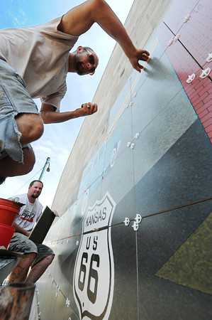 Globe/T. Rob Brown<br /> Branden Yost of Joplin (above) and Jason Cook, both RC Tile & Hardwoods installers, work on a Route 66 mural in downtown Galena, Kan., Tuesday afternoon, June 26, 2013. The mural, designed by art director Chris Auckerman and graphic designer Jon White, both with Images in Tile owned by Paul Whitehill, is located at the intersection of 7th and Main streets in Galena.