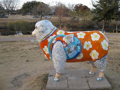 "Welcoming ""Ewe""  San Angelo Convention & Visitors Bureau, 418 W. Avenue B (river side) Orange dress, camera over shoulder and a travel pack."