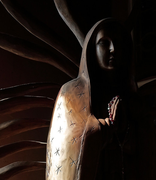 Old, partly charred wood statue of Mary - Virgin of Guadalupe church
