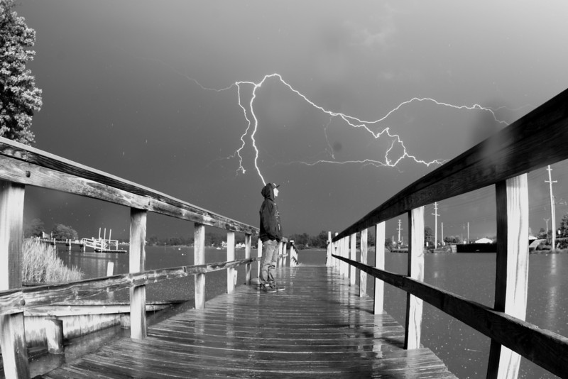 This photograph is one of the most dangerous ones I have created.  I was trying to get the lightning to go off behind my subject and then I would provide the lighting for the subject in the foreground.  Instead, the lightning hit the building 100 yards behind us lighting up the entire surrounding area before also reaching out into the sky in the background directly behind the subject.  And to those who have never been this close to a lightning strike it felt like bomb going off.  This is the original photograph although I did darken and make it black and white I DID NOT alter the content in the photograph itself, this is real.