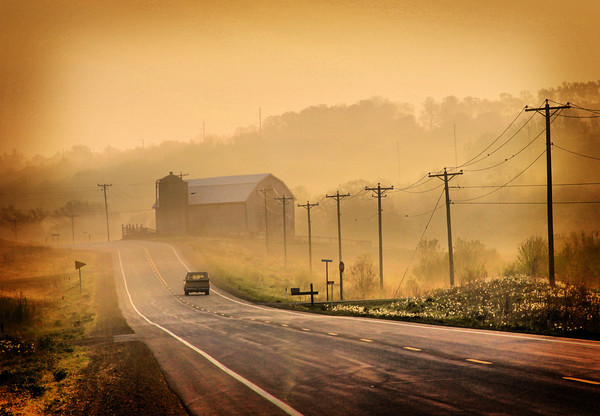 The pickup truck travels down the country road early in the spring morning.