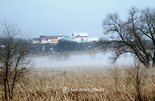 Across the field and fog is the New Glarus Brewing Company on the hill.