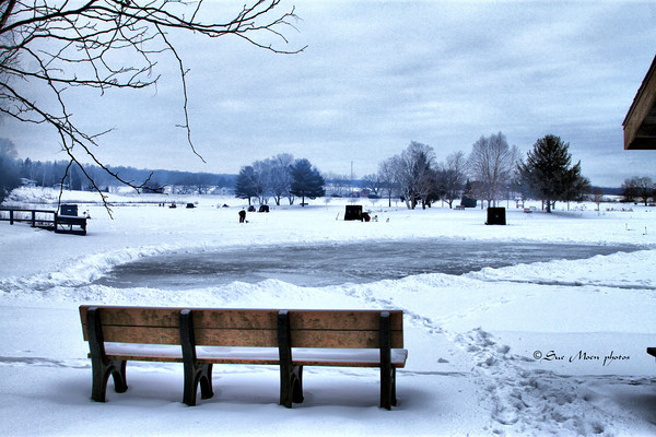 Looking past a bench at the edge of Lake Montesian there's an ice rink and some of the shelters for the annual fisheree.