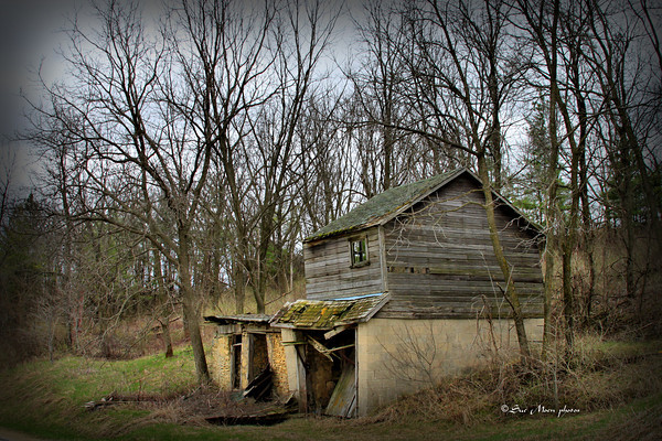 The shed, unused for many years,  sits next to a country road.