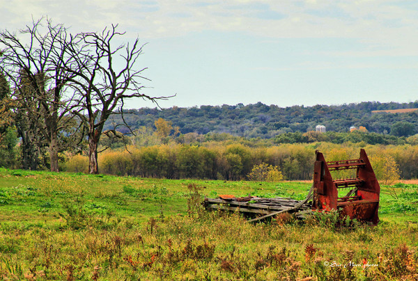 A piece of machinery sits in a pasture.