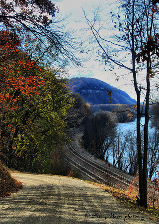 A gravel road above the Mississippi River and the railroad tracks that run parallel to the river.