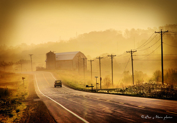 The pickup truck travels down the country road early on a slightly foggy spring morning.